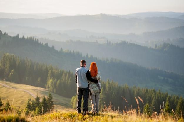 Couple de randonneurs romantique sur une colline, profitant du magnifique paysage de montagne Photo Premium