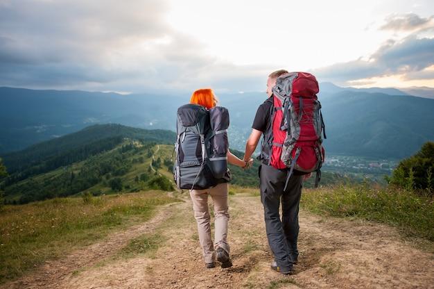 Couple de randonneurs avec sacs à dos sur la route en montagne Photo Premium