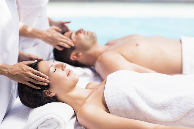Couple recevant un massage de la tête d'un masseur dans un spa Photo Premium