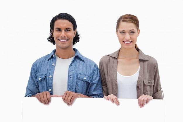 Couple à la recherche sur le mur blanc Photo Premium