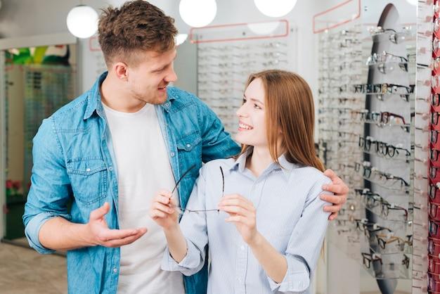 Couple à la recherche de nouvelles lunettes chez l'optométriste Photo gratuit
