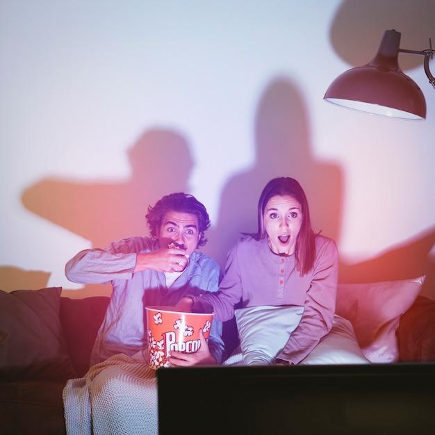 Couple regardant un film d'horreur Photo gratuit
