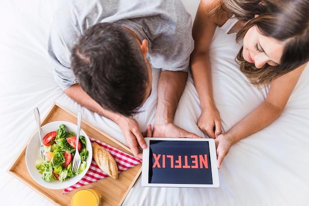 Couple regardant la série netflix près du plateau avec de la nourriture Photo gratuit