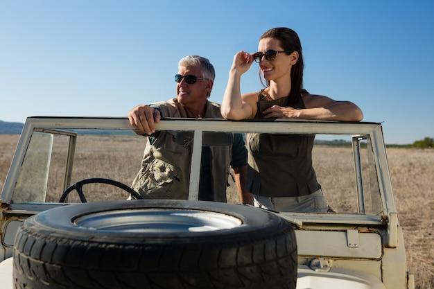 Couple, regarder loin, debout, dans, véhicule, sur, champ Photo gratuit