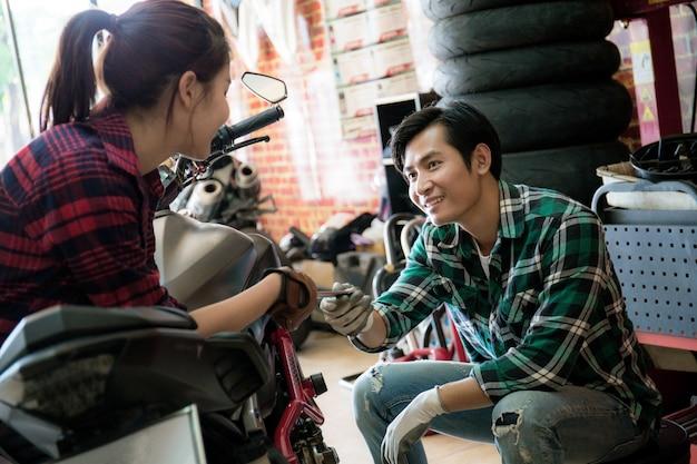 Un couple répare une moto Photo Premium