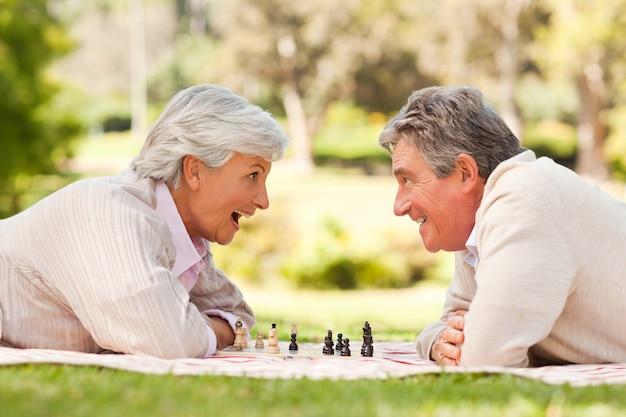 Couple retraité jouant aux échecs Photo Premium