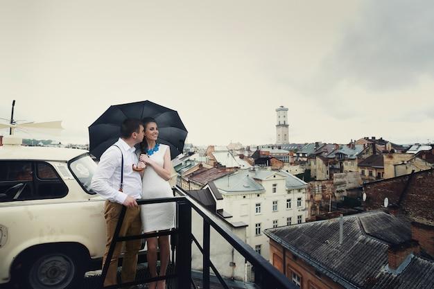 Le couple de rêve pose sous le parapluie sur le toit Photo gratuit