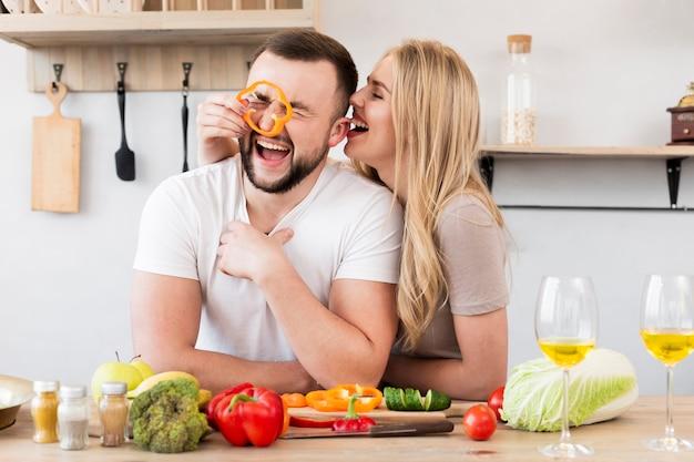 Couple riant jouant avec poivron Photo gratuit
