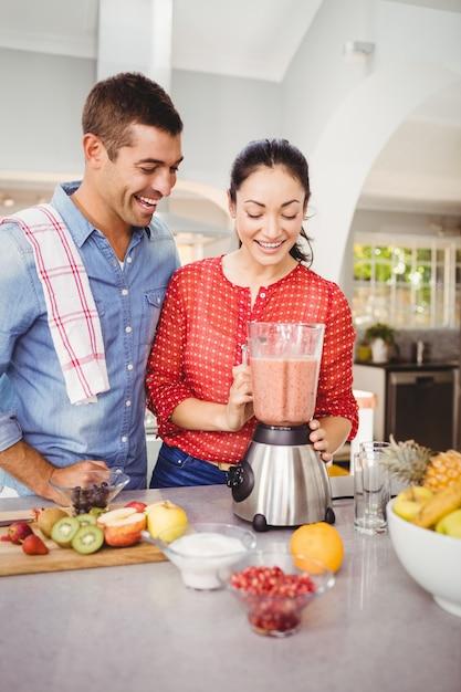 Couple riant avec jus de fruits Photo Premium