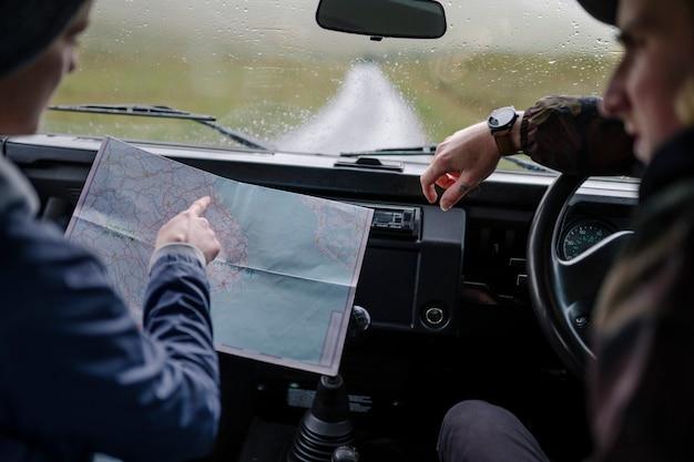 Couple sur un road trip en vérifiant la carte Photo Premium