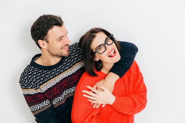 Couple romantique amoureux s'embrassent et s'amusent ensemble, portent des chandails chauds, tricotés contre un blanc Photo Premium