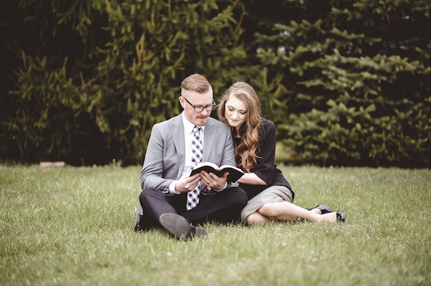 Couple Romantique Assis Sur La Pelouse Et Lire Avec Amour Un Livre Photo gratuit