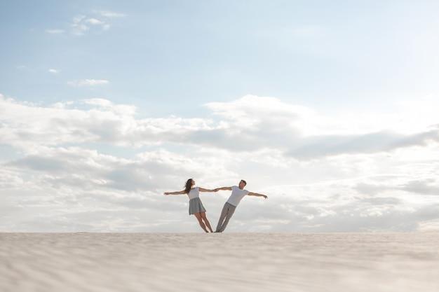 Couple romantique dansant, se tenant les bras dans le désert de sable Photo Premium
