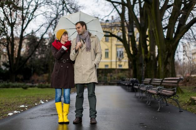 Couple romantique à pied sous la pluie Photo Premium