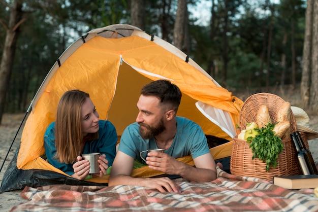 Couple s'allongeant dans la tente se regardant Photo gratuit