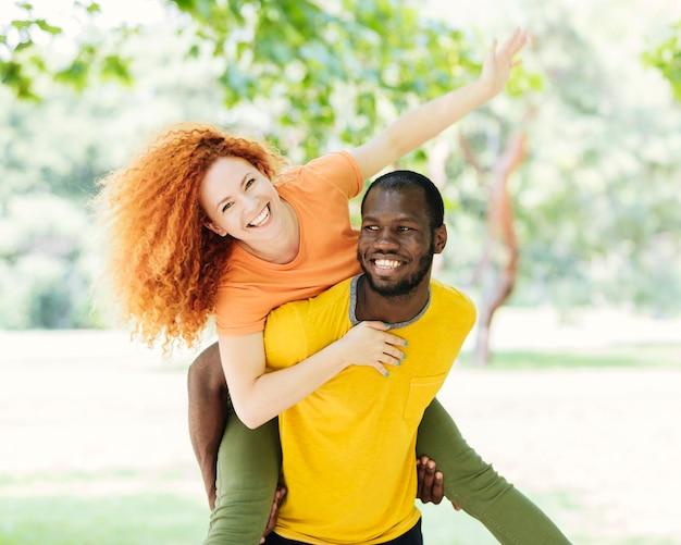 Couple s'amuser dans le parc Photo gratuit