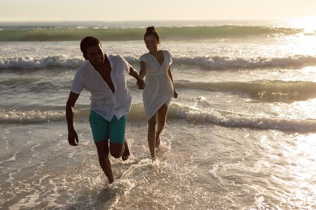 Couple s'amuser ensemble sur la plage Photo gratuit