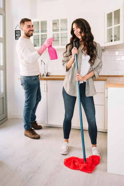 Couple s'amuser tout en nettoyant la cuisine Photo gratuit