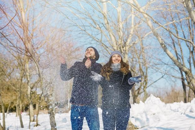 Couple s'amuser à winter park en vomissant de la neige par journée ensoleillée. Photo Premium