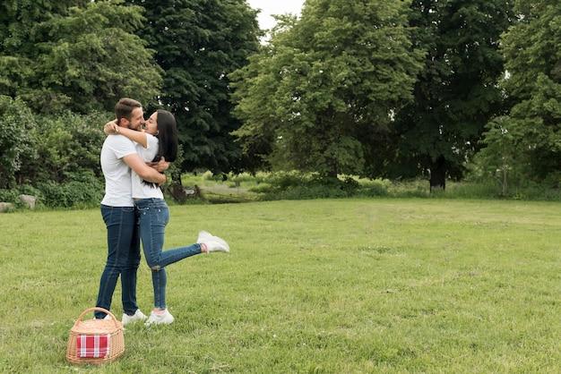 Couple s'embrassant au parc Photo gratuit