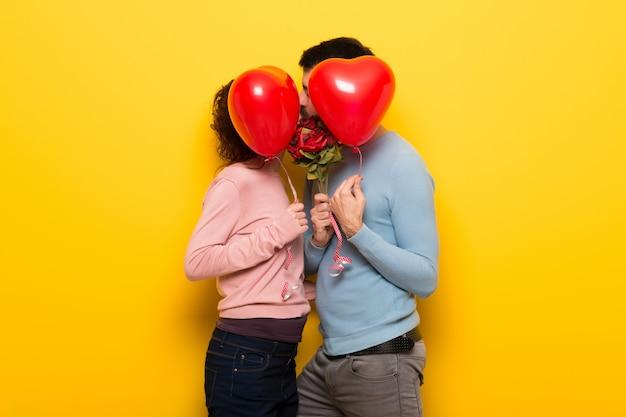 Couple en saint valentin avec des fleurs et des ballons en forme de cœur Photo Premium