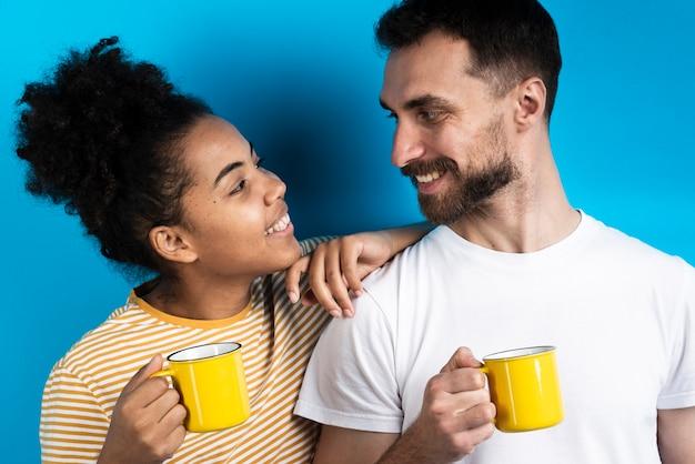 Couple Se Regardant En Tenant Des Tasses Photo gratuit