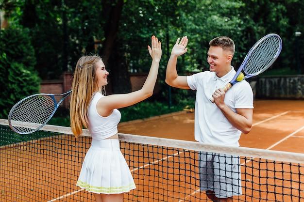 Couple se serrant la main sur le court de tennis après une partie .. Photo Premium