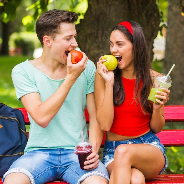 Couple, séance, banc, manger, pommes mûres, tenue, smoothies Photo gratuit