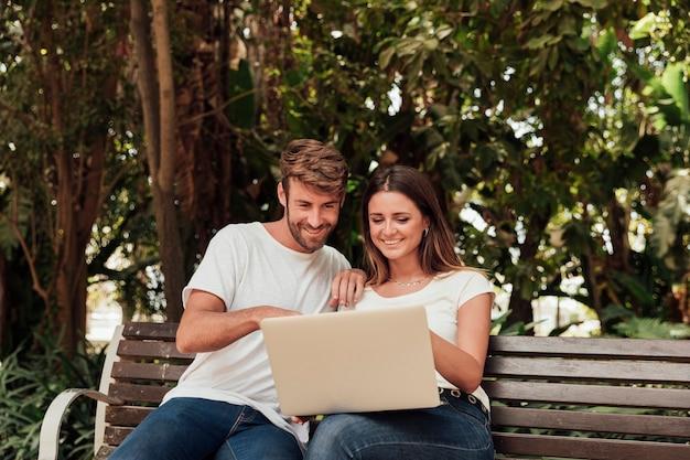 Couple, séance, banc, ordinateur portable Photo gratuit