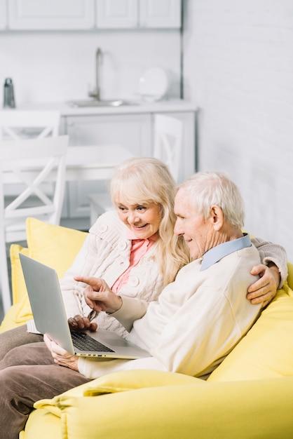 Couple senior à l'aide d'un ordinateur portable Photo gratuit