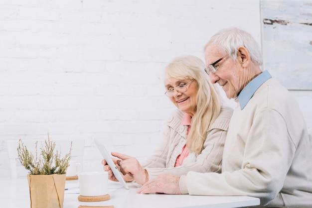 Couple senior à l'aide d'une tablette Photo gratuit