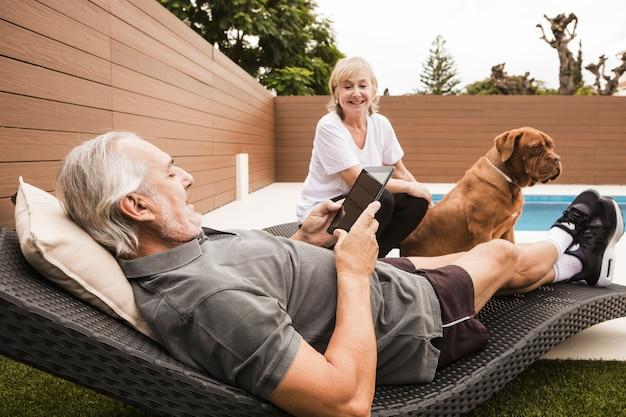 Couple senior avec chien dans le jardin Photo gratuit