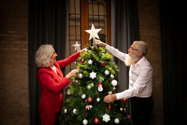 Couple senior prépare l'arbre de noël Photo gratuit
