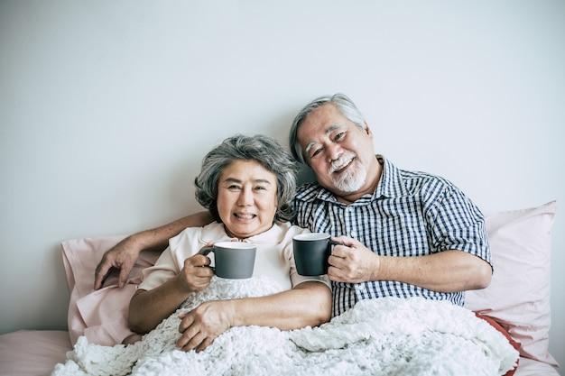 Couple senior rire tout en buvant du café dans la chambre Photo gratuit