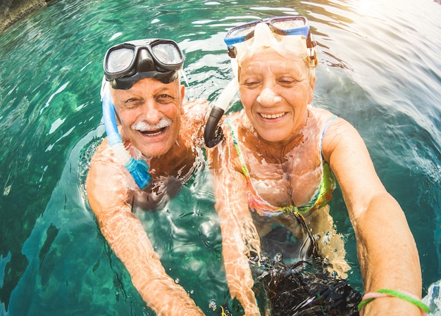 Couple senior s'amuser plongée en apnée sur une plage tropicale Photo Premium