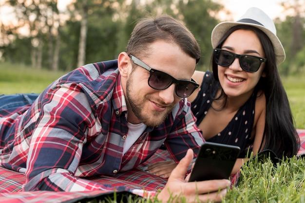 Couple avec un smartphone sur une couverture de pique-nique Photo gratuit