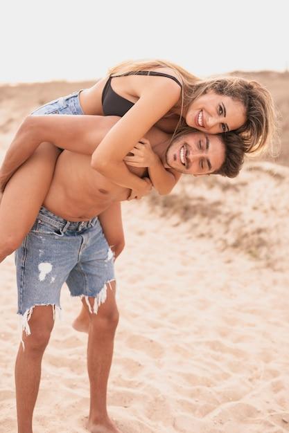 Couple smiley à la plage s'amuser Photo gratuit