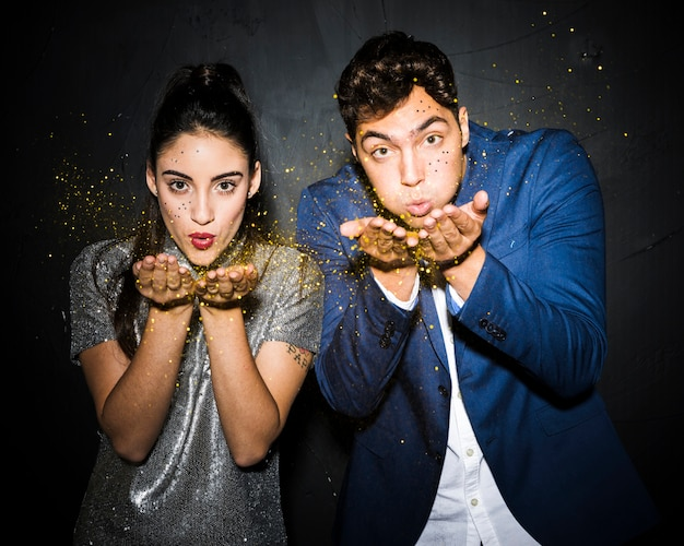 Couple soufflant des paillettes d'or Photo gratuit