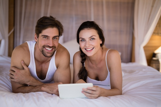Couple souriant, à l'aide de tablette numérique, sur, lit, dans, cottage Photo gratuit