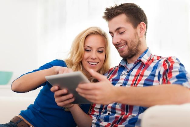 Couple Souriant à L'aide De Tablette Numérique à La Maison Photo gratuit