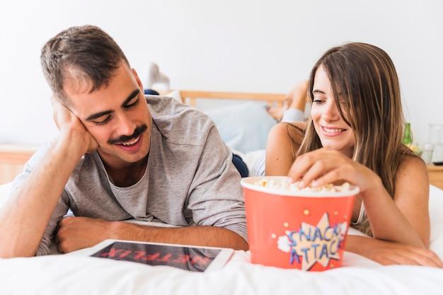 Couple souriant en appréciant le pop-corn et la série netflix Photo gratuit