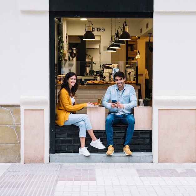 Couple souriant, assis dans la zone de la cafétéria ouverte Photo gratuit