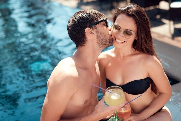 Couple souriant, buvant des cocktails au bord de la piscine Photo Premium