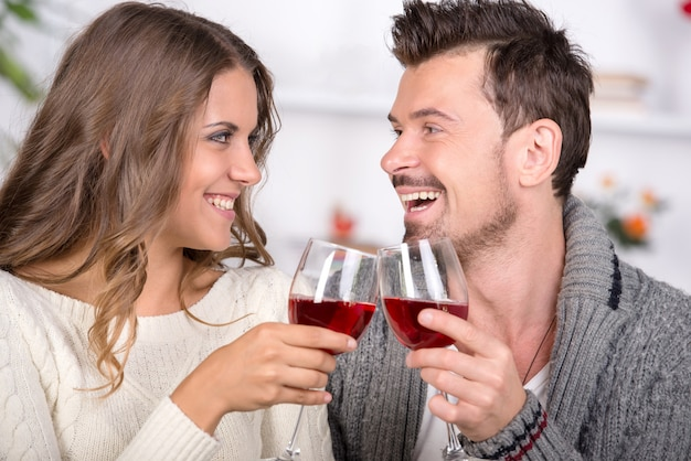 Couple souriant datant et buvant du vin rouge à la maison. Photo Premium
