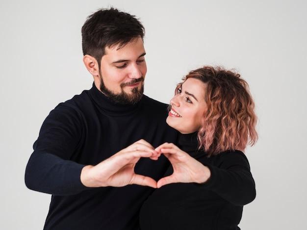 Couple souriant et faisant forme de coeur avec les mains Photo gratuit