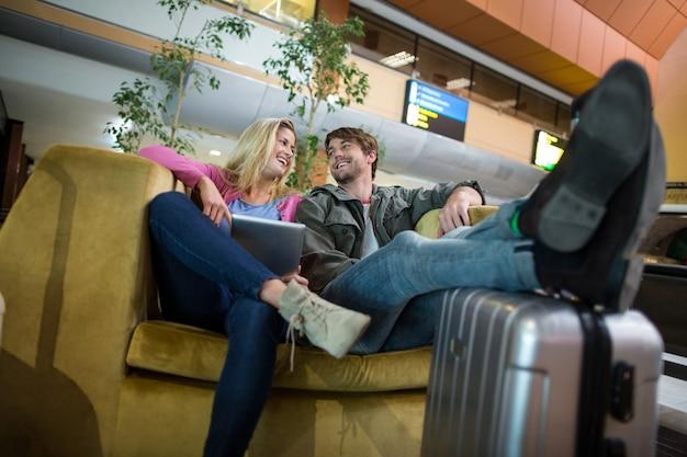 Couple Souriant Interagissant Les Uns Avec Les Autres Dans La Zone D'attente Photo gratuit