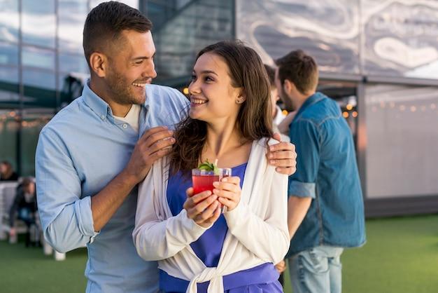 Couple souriant lors d'une fête Photo gratuit