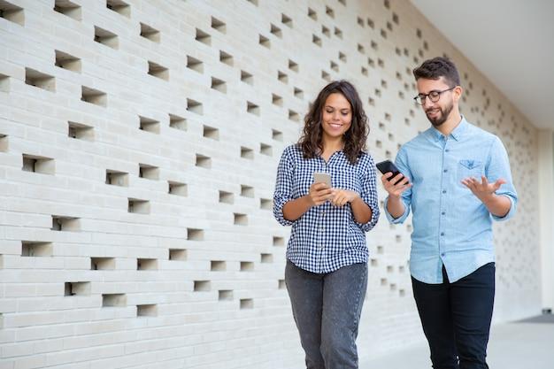 Couple Souriant Marchant Et Utilisant Des Smartphones Photo gratuit