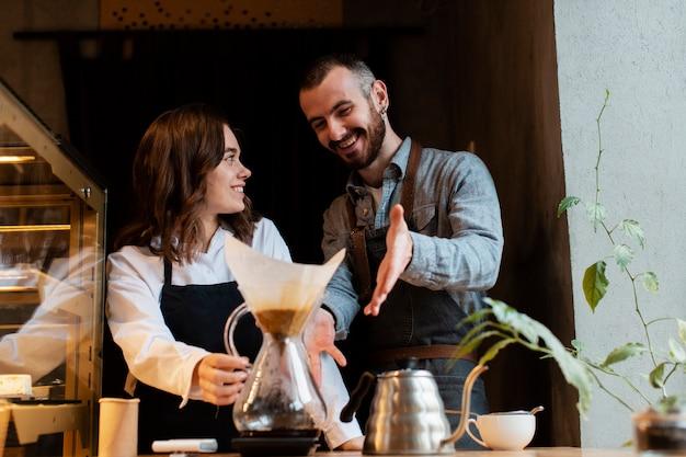Couple souriant et pointant au filtre à café Photo gratuit