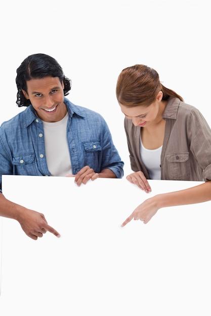 Couple souriant pointant vers le bas sur un mur blanc Photo Premium
